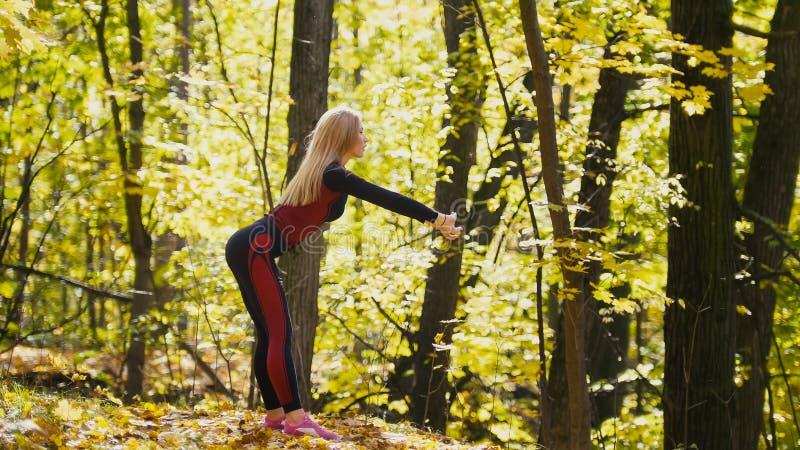 La muchacha que tiene un entrenamiento se resuelve en el parque del otoño Modelo rubio del aptitud-bikini atractivo en traje rojo foto de archivo libre de regalías