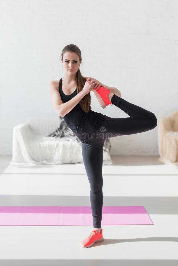 La muchacha que trabaja estirando la pierna muscles calentamiento en foto de archivo