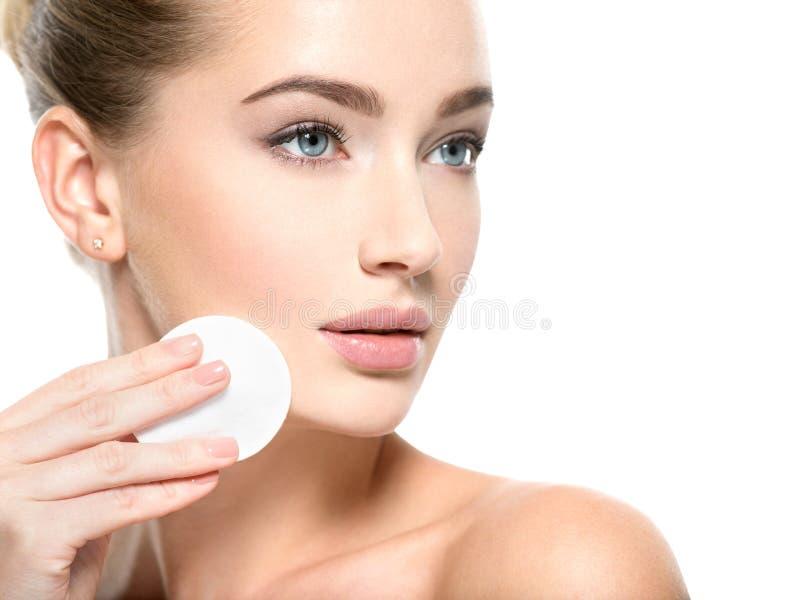 La muchacha quita la bola de algodón del maquillaje de cara foto de archivo
