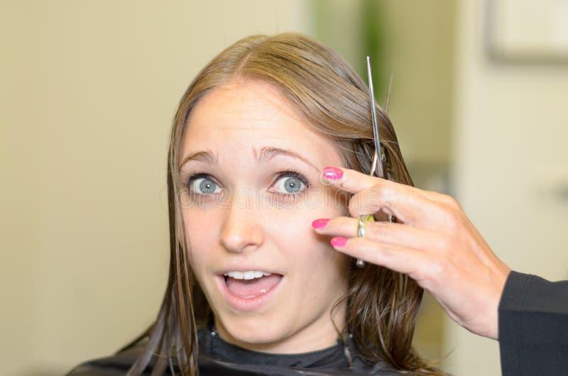 La muchacha reacciona al estilista para cortar su cortocircuito del pelo fotos de archivo
