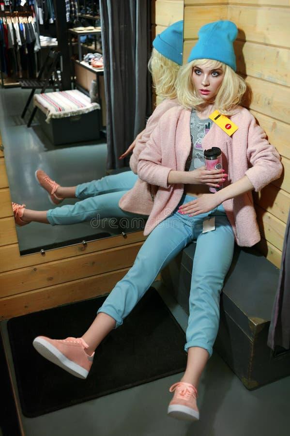 La muchacha real parece una muñeca de barbie en tienda en venta La muchacha se vistió en ropa azul y rosada en colores pastel de  imagen de archivo
