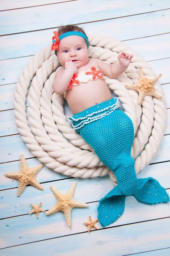 La muchacha recién nacida en un traje de la sirena, mentiras en las cuerdas en los tableros de madera foto de archivo