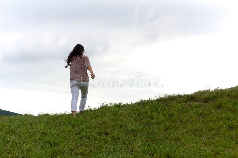 La muchacha remata la colina verde herbosa fotos de archivo
