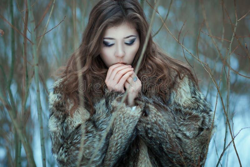 La muchacha respira en las manos frías fotografía de archivo