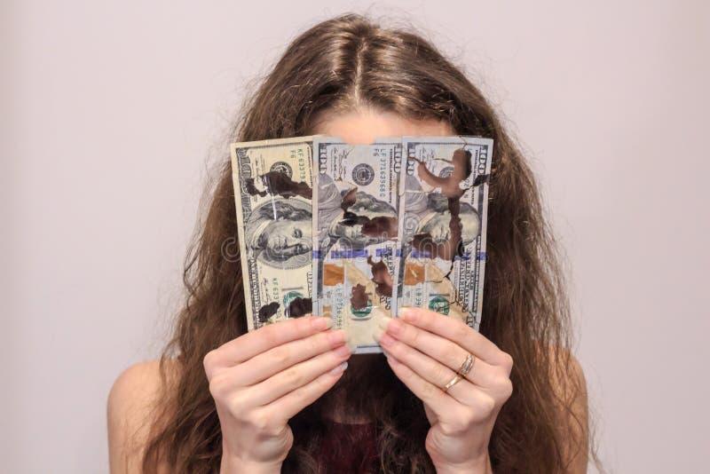 La muchacha rizada guarda billetes de dólar foto de archivo libre de regalías