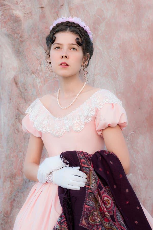 La muchacha romántica en un vestido de noche se coloca cerca de una pared del sto rosado imagenes de archivo