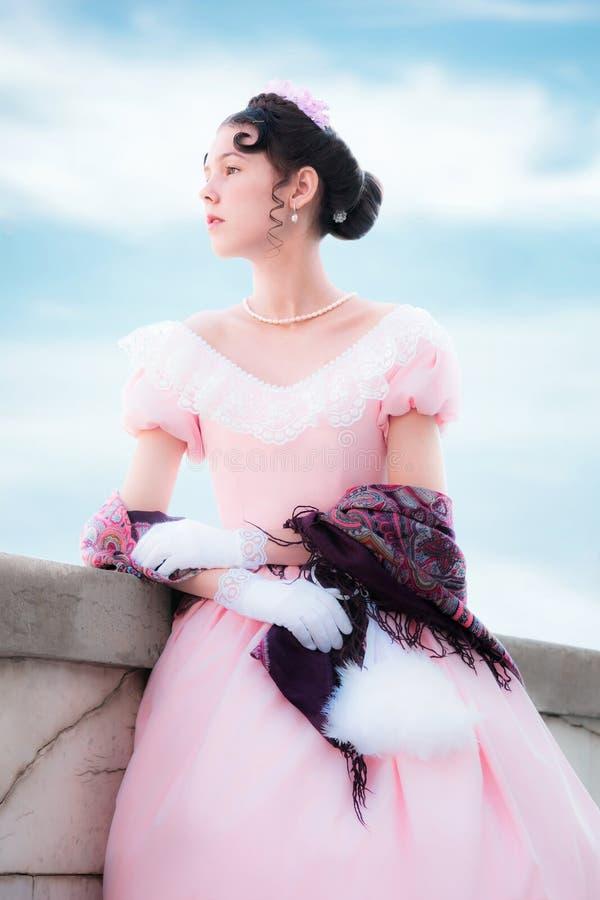 La muchacha romántica en vestido de noche se está colocando en el balcón foto de archivo libre de regalías