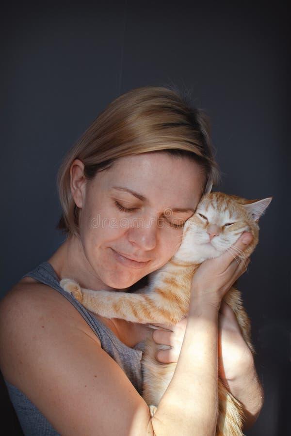 La muchacha rubia abraza y besa un gato rojo en un cuarto soleado con una pared gris foto de archivo