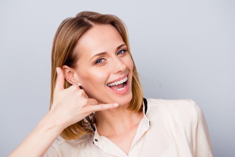 La muchacha rubia alegre con sonrisa de emisión está gesticulando para llamarla fotografía de archivo libre de regalías