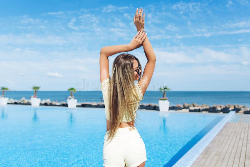 La muchacha rubia atractiva con el pelo largo se est? colocando cerca de piscina Ella lleva los pantalones cortos cortos amarillo fotos de archivo libres de regalías