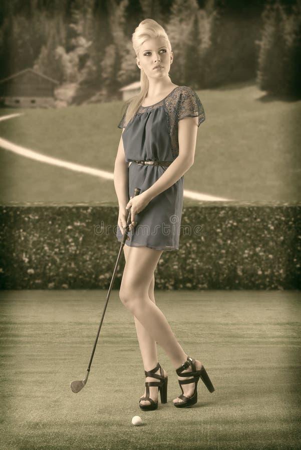 La muchacha rubia atractiva paga golf, en un estilo de la vendimia fotos de archivo