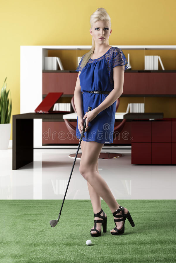 La muchacha rubia atractiva paga golf, mira adentro a la lente fotos de archivo