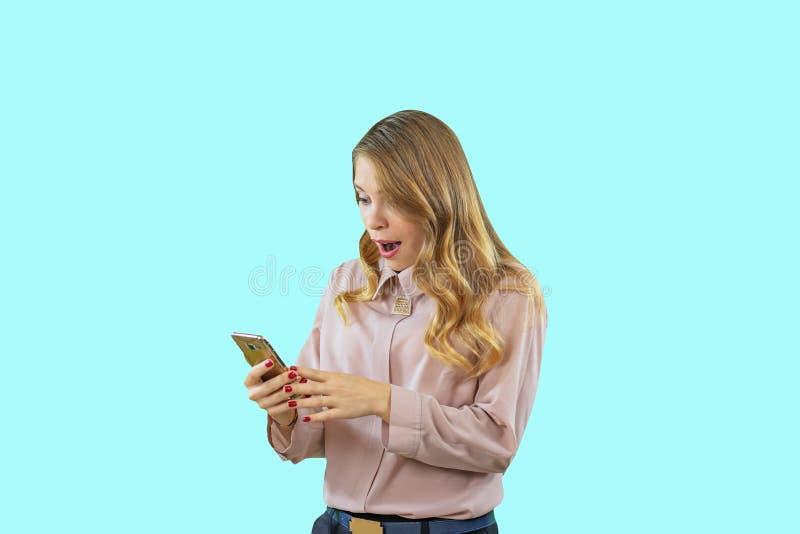 La muchacha rubia atractiva y alegre en una camisa se está colocando de lado y está mirando el teléfono en su mano en aislada imagen de archivo
