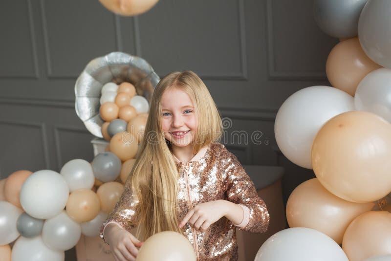 La muchacha rubia bastante pequeña juega en un estudio con encendido los globos foto de archivo