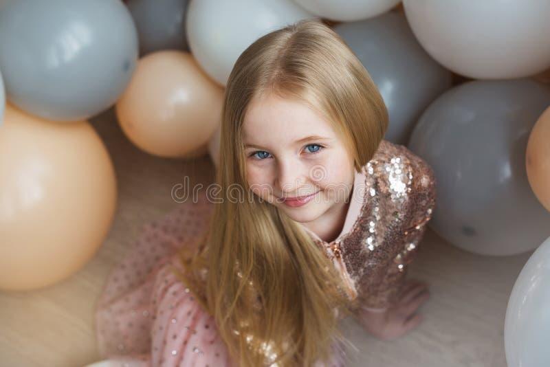 La muchacha rubia bastante pequeña se sienta y sonríe en piso con los globos foto de archivo libre de regalías