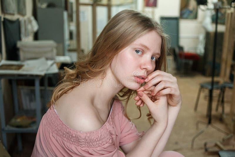 La muchacha rubia bonita joven con los ojos azules en vestido rosado se sienta en el taller, llevando a cabo las manos cerca de c imagen de archivo