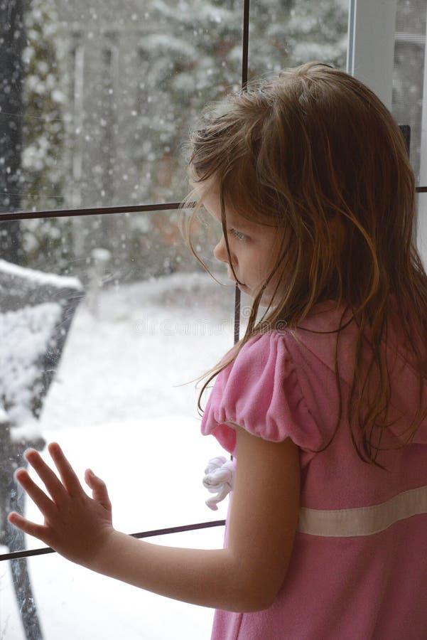 La muchacha rubia caucásica joven se inclina en la puerta de cristal francesa y mira los copos de nieve que caen afuera fotos de archivo libres de regalías