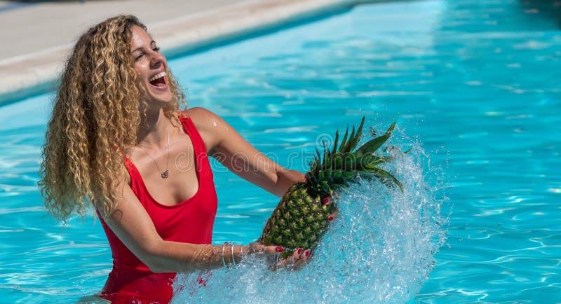 La muchacha rubia caucásica juega con una piña en la piscina fotografía de archivo libre de regalías