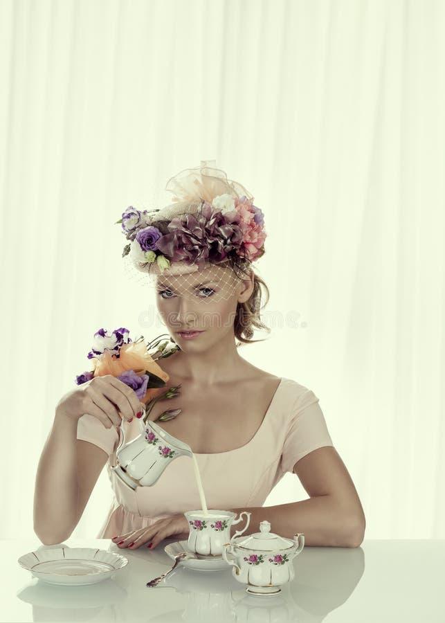 La muchacha rubia con el juego de té clásico toma el jarro de leche fotografía de archivo libre de regalías