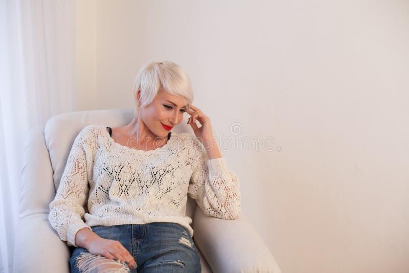 La muchacha rubia con el pelo corto se sienta en una butaca blanca imagen de archivo libre de regalías
