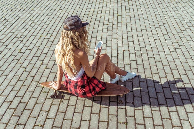 La muchacha rubia con el pelo largo, ciudad del verano sienta el monopatín, lee el uso del mensaje en línea, las redes sociales M fotografía de archivo libre de regalías
