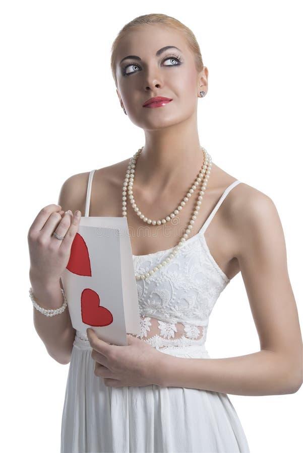 La muchacha rubia con la postal de la tarjeta del día de San Valentín mira para arriba fotos de archivo libres de regalías