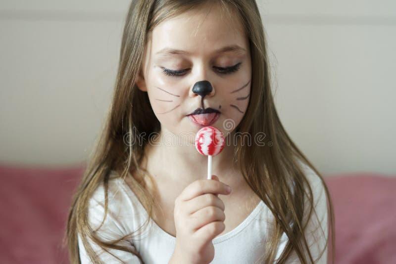 La muchacha rubia con un maquillaje que imita un gato lleva a cabo en su mano chups de un chupa imágenes de archivo libres de regalías