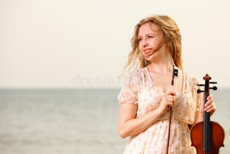 La muchacha rubia con un violín al aire libre fotos de archivo