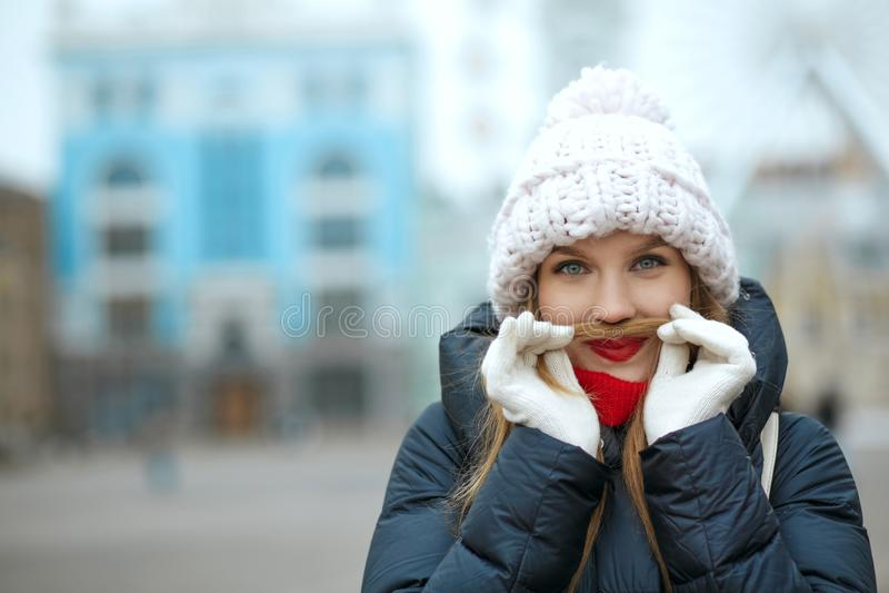 La muchacha rubia coqueta que se divierte muestra el bigote de su pelo Emp fotos de archivo