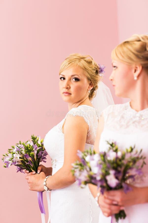 La muchacha rubia de la novia hermosa con el maquillaje brillante blanco del vestido y del peinado de boda mira en el espejo foto de archivo libre de regalías