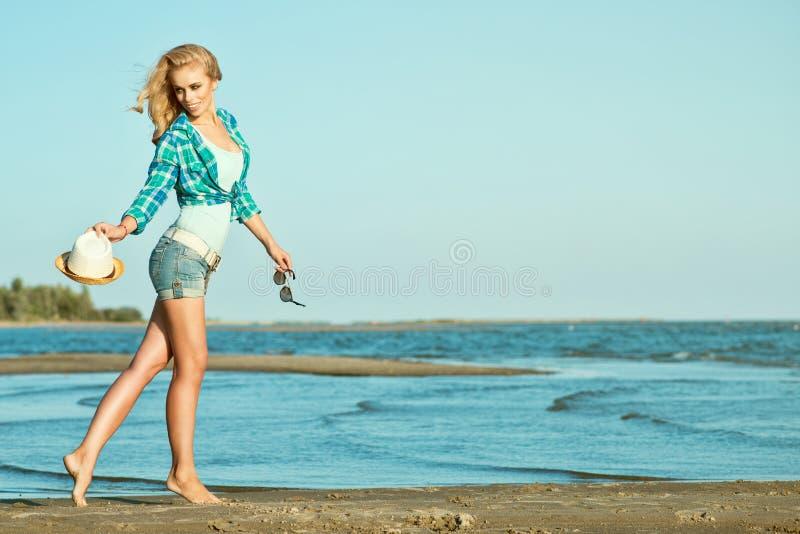 La muchacha rubia delgada hermosa joven está corriendo a lo largo de la playa con el sombrero y las gafas de sol en sus manos imagenes de archivo