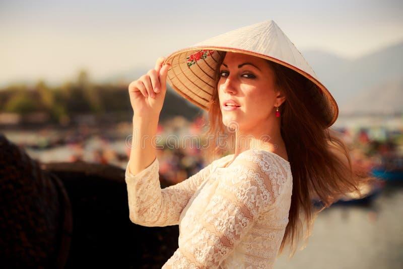 la muchacha rubia en el vestido blanco toca sonrisas del sombrero en la barrera fotografía de archivo libre de regalías