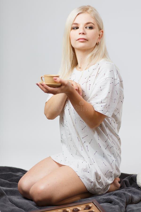 La muchacha rubia en una camiseta blanca se está sentando en una tela escocesa gris en fotos de archivo