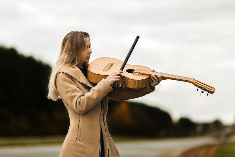 La muchacha rubia en una capa del beige toca la guitarra como un violín que se coloca al borde de la autopista del otoño imágenes de archivo libres de regalías