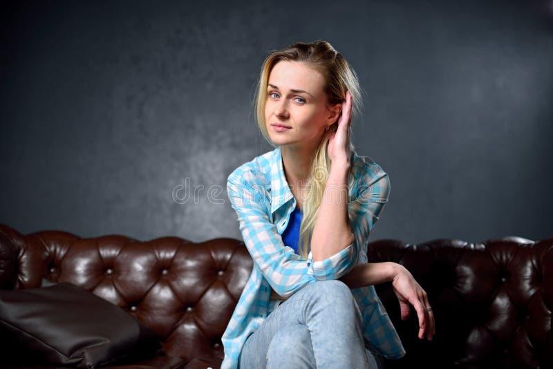 La muchacha rubia en vaqueros se sienta en el sofá de cuero imagenes de archivo