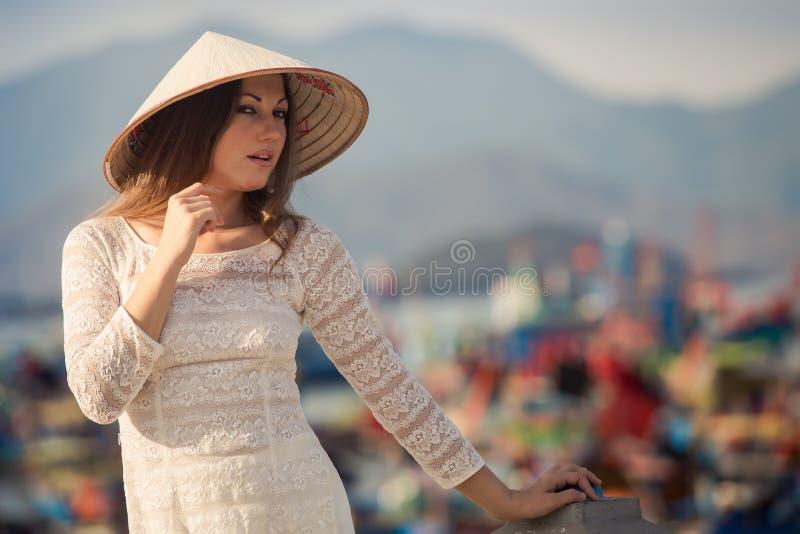 la muchacha rubia en vestido del vietnamita se inclina en el terraplén foto de archivo libre de regalías