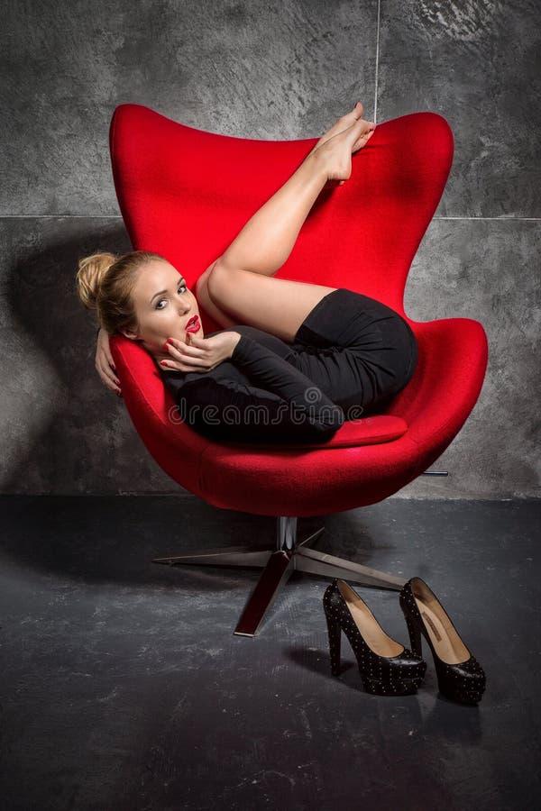 La muchacha rubia en vestido negro miente en la butaca roja imágenes de archivo libres de regalías