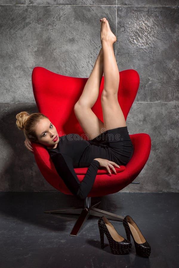 La muchacha rubia en vestido negro miente en la butaca roja imagen de archivo libre de regalías