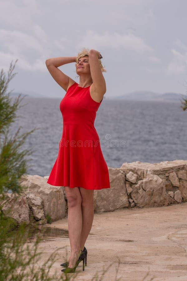 la muchacha rubia en vestido rojo se está colocando cerca del mar foto de archivo