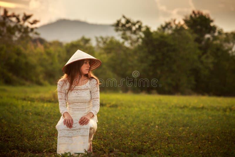 la muchacha rubia en vietnamita se viste y el sombrero se pone en cuclillas en campo imágenes de archivo libres de regalías