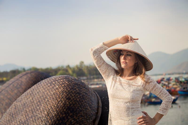 la muchacha rubia en vietnamita viste el sombrero de los tactos por la barrera fotografía de archivo