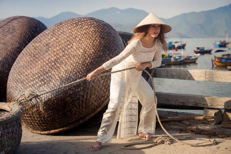la muchacha rubia en vietnamita viste la cuerda de tirones en el terraplén foto de archivo