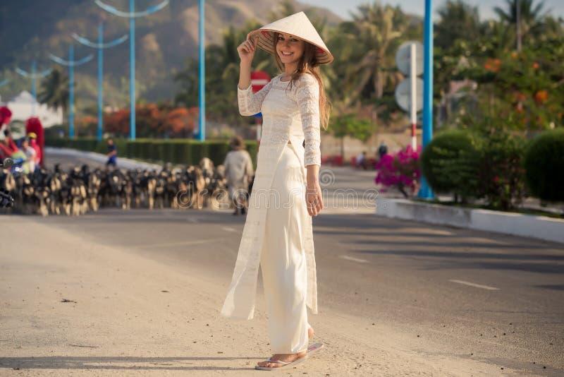 la muchacha rubia en vietnamita viste paseos contra multitud de las cabras imagen de archivo