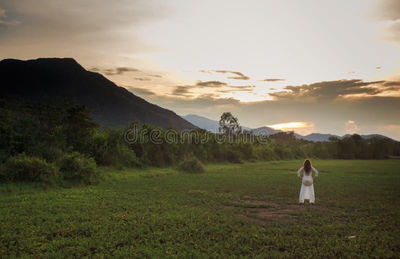la muchacha rubia en vietnamita viste posiciones en cuclillas en campo de hierba fotografía de archivo libre de regalías