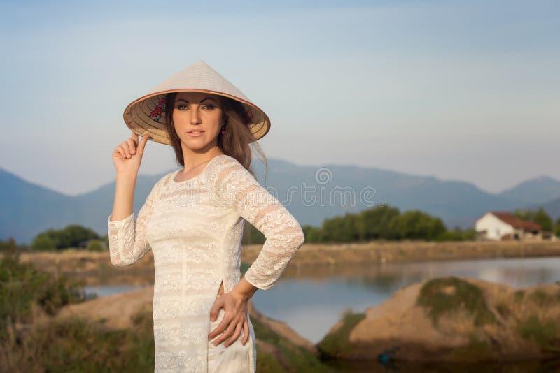 la muchacha rubia en vietnamita viste sonrisas contra los lagos del país fotos de archivo