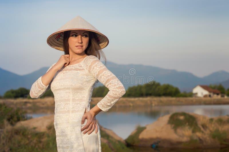 la muchacha rubia en vietnamita viste sonrisas contra los lagos del país fotografía de archivo libre de regalías