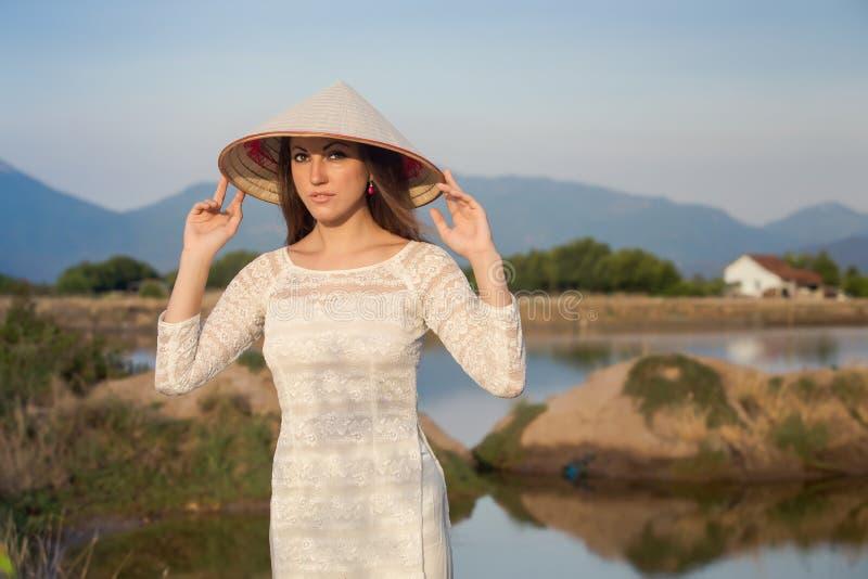 la muchacha rubia en vietnamita viste sonrisas contra los lagos del país imágenes de archivo libres de regalías