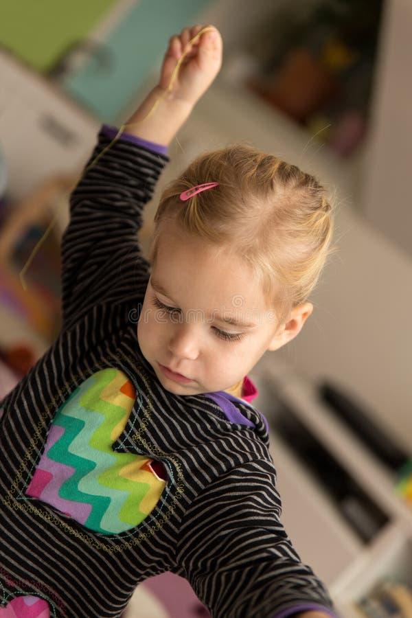 La muchacha rubia está jugando con algodón de costura imagen de archivo