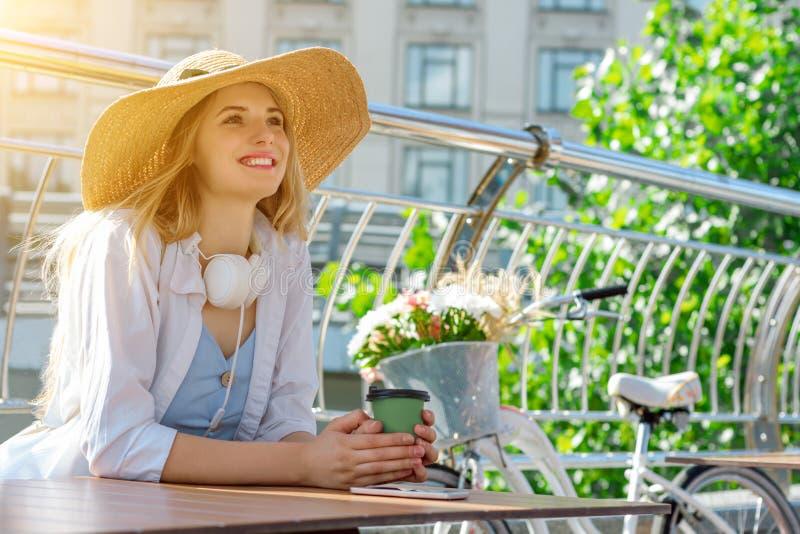La muchacha rubia feliz está bebiendo el café, la música que escucha y el sueño fotos de archivo libres de regalías