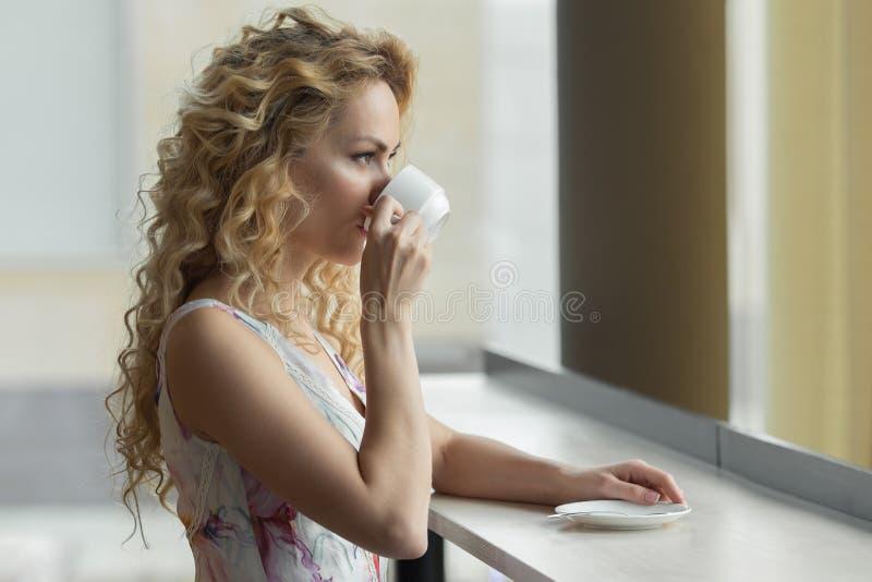 La muchacha rubia hermosa bebe una taza de café o de té caliente en café fotos de archivo